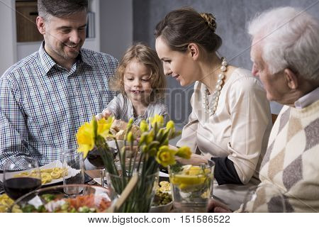 Smiling young marriage with a little child sitting at a table during an elegant family meeting