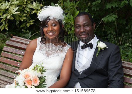 Happy Newly Wed African American Couple On A Bench