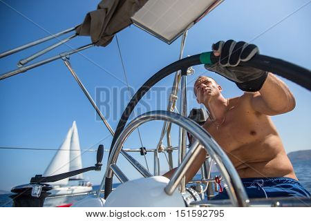 Skipper drive a sailing boat during a race on the regatta.