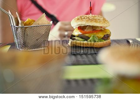 Eating out during an afternoon date (rendezvous) with dining in the burger buffet symbolized as large burger on the black stony plate in front of a pink lady