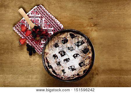 Homemade traditional tart dessert on a wooden table closeup. Fresh berry tart. Top view