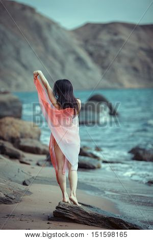 Young nude woman with hair flying against the sea background