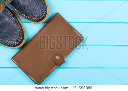 Men's accessories with brown purse and shoes. Top view on the wooden background.