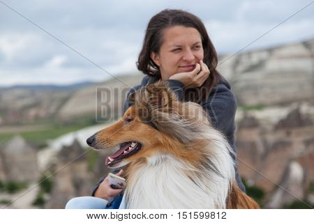 Young girl squints and collie looking in different directions