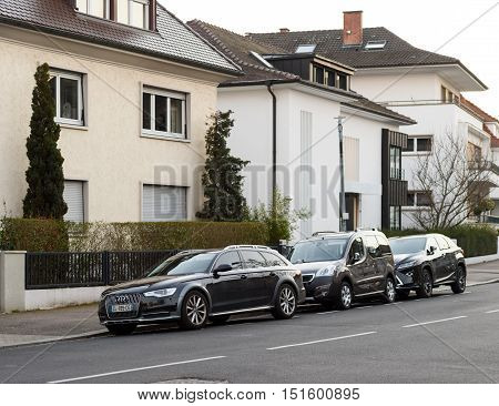 STRASBOURG FRANCE - MAR 18 2016: AUDI wagon Peugeot Car and Lexus Luxury SUV parked in front of luxury houses on calm city street neighborhood