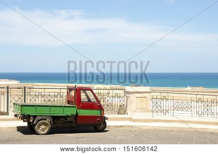 Three wheeler vehicle background sea blue sky