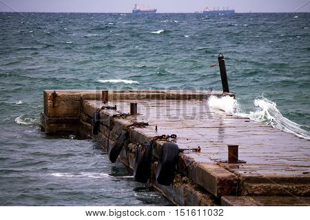 Old pier with rustly bollards and fenders with two vessels on the background