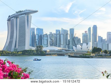 Singapore, Republic of Singapore - May 4, 2016: motorboat crossing Marina Bay. Cloud garden and supertrees grove fviewed from Marina East park with flowers on foreground