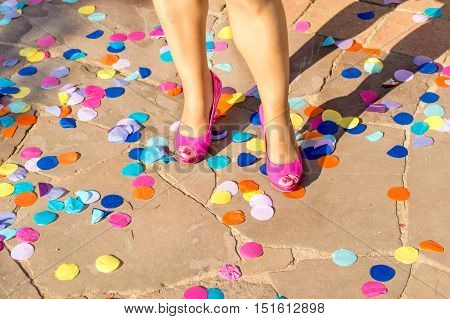 Closeup of woman s shoes at a party with colorful confetti
