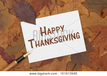 Happy Thanksgiving Greeting Card Some fall leaves pen and a greeting card with text Happy Thanksgiving