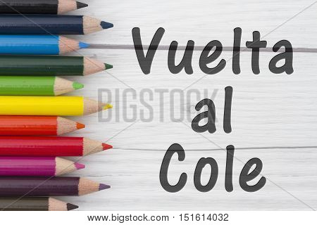Pencil Crayons with text Vuelta al Cole Spanish Back to School with weathered wood background