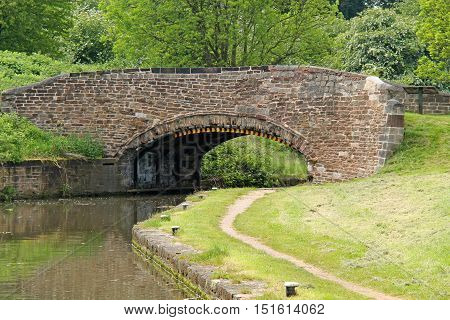 A Classic Stone Built Bridge Over a Canal and Towpath.