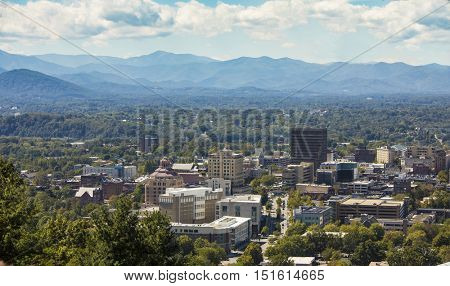 Low aerial shot of downtown Asheville, North Carolina and surrounding mountains