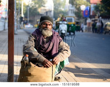 AHMADABAD GUJARAT INDIA - JANUARY 30: The poor Indian peasant is waiting for the bus squatting by the sack with the rice in the Ahmedabad city in the Gujarat state in India Ahmadabad in January 28 2015