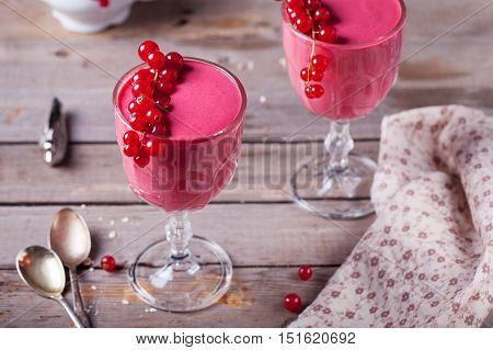 Smoothie, dessert with raspberry and oatmeal in glasses decorated with fresh redcurrant branch on a wooden background.