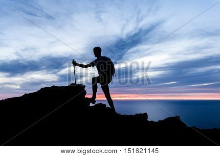 Man hiking silhouette in mountains sunset and ocean inspirational landscape. Male hiker with walking sticks on top of mountain looking at beautiful night sea landscape.