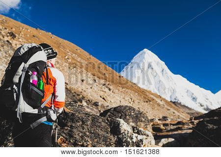 Woman Hiker Hiking in Himalaya Mountains in Nepal. Trekking with backpack in Himalayas to Everest Base Camp. Travel Exploration and Fitness Concept. Sunny Day with Pumori Summit in Background.