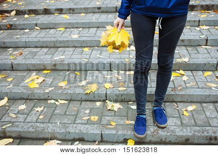 Part Of Body People Cold Rainy Autumn Concept. Sporty Legs Blue Jeans And Sneakers. Woman In Blue Wi