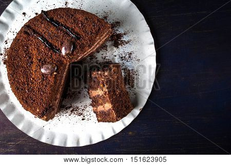 Chocolate cake with cream on a blue wooden table. One piece of cake is on the plate, girl eats it, hand in the picture, top view, copy space
