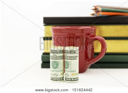 Careful accounting and investment work reflected in red mug United States money books and pencils. Selective focus on currency. White background with copy space.
