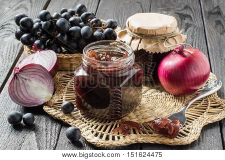 Red onion jam (onion confiture) with grapes in glass jars and ingredients for its preparation on a straw napkin and a wooden table. French cuisine. Selective focus
