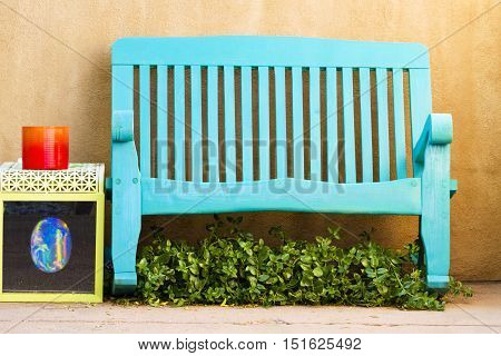Blue bench offers outdoor seating in a Santa Fe New Mexico courtyard. Location is Canyon Road a popular art district and tourist destination.