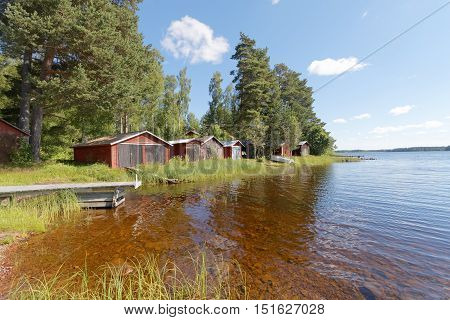 Group of red boathouse by the waterside in warm evening light pine trees and blue sky in the background