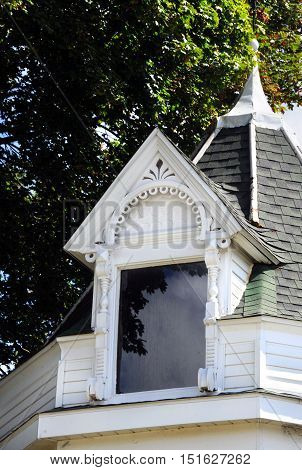 Beautiful window dormer is wooden and painted white. Architecture is intricate and beautiful.