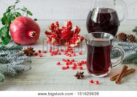 Cap of pomegranate juice or cocktail, ripe pomegranate, slices, seeds, cinnamon, star anise, jug, fir branches on a light white wooden background. Pomegranate juice cocktail, pomegranates. Horizontal.