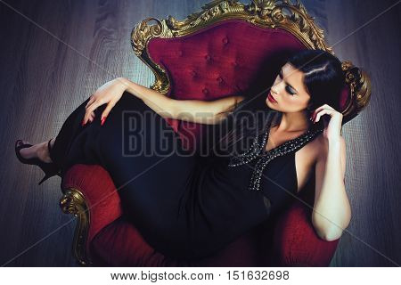 Elegant woman with evening dress sitting on a baroque armchair