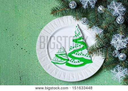 The idea of Christmas decoration for the table setting. Homemade decor for serviette in the form of a Christmas tree on a plate. Decorated Christmas tree branch on a green background