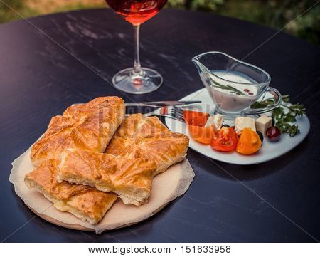 Oven-fresh delicious pie filled with home made cheese. Gourmet traditional georgian khachapuri surrounded by white sauce cheese black olives sliced tomatoes and glass of red wine.