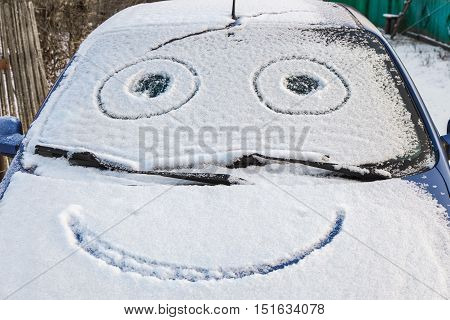 Snow covered car with drawn smile in windshield