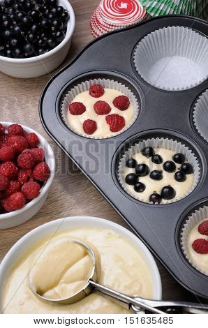 Preparation for baking muffins stuffed with raspberries and black currants