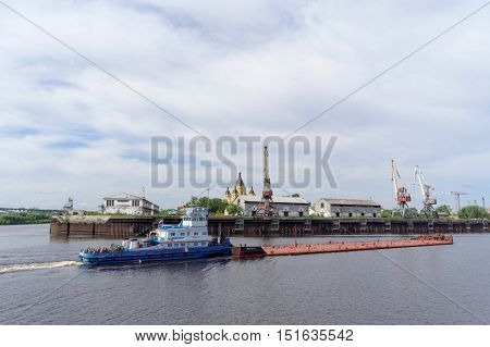 Nizhny Novgorod, Russia. - June 2.2016. River tug Ural-7 pushes a barge at Strelka - the intersection of the rivers Volga and Oka in front of river port