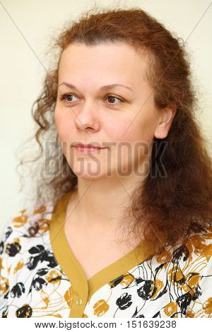 Portrait of smiling happy curly woman looks away in home robe