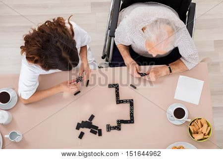 High Angle View Of Elder Woman Playing Domino Game With Her Nurse