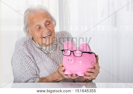 Happy Senior Woman Holding Piggybank At Home