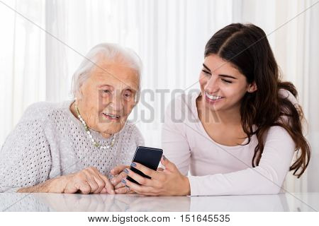 Young Woman Teaching Her Grand Mother How To Use Smartphone At Home