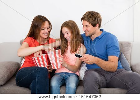 Happy Family Sitting On Sofa Eating Popcorn At Home
