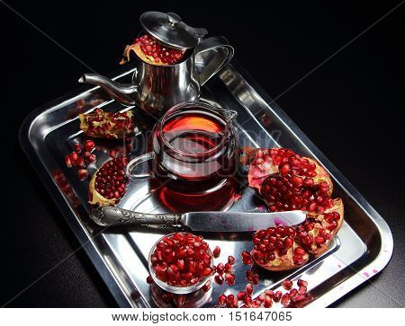 pomegranate and garnet juice on a metal dish with a teapot and a knife