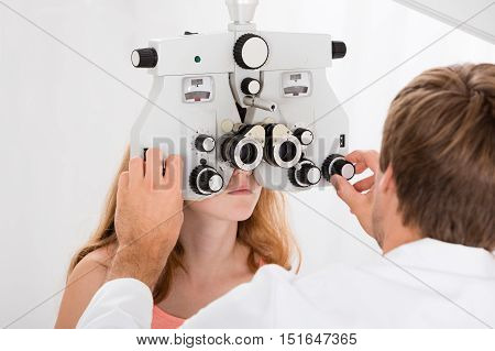 Young Male Optometrist Doing Sight Testing For Girl