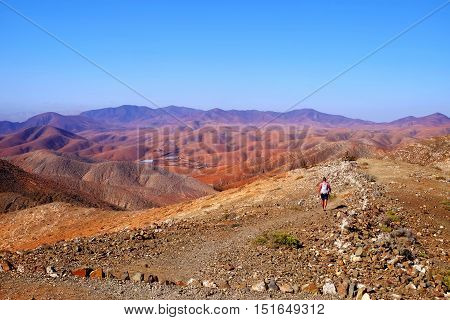 A magnificent mauntains landscape and a small figure of a tourist. Location is the observatory in Fuerteventura.