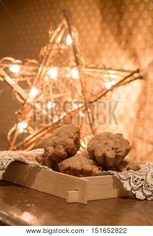 Muffins with apples and cinnamon on wood table near Christmas light.