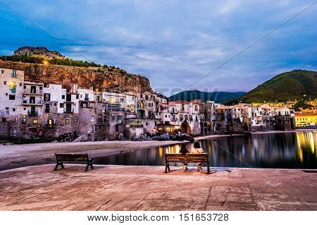 Unrecognizable couple on a bench with view on habour and old houses in Cefalu at night, Sicily. Beautiful townscape of old italian town. Travel photography.