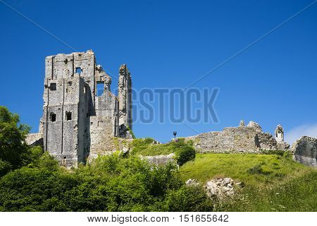 The sun beats down on the stone walls and village of Corfe Castle in Dorset on a hot summer day