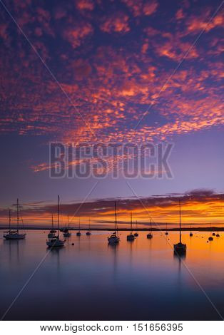 Deep colours emanate from the sunset illuminating clouds and the calm seas of Poole Harbour at Rockley