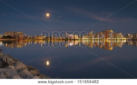 Perfect reflections are cast on the still harbour waters with the bright lights of Poole's backwater developments illuminating the view. The moon also reflects in the sea water