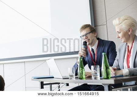 Businessman speaking through microphone while sitting at desk in convention center