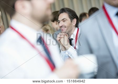 Thoughtful businessman with hands clasped at lobby in convention center